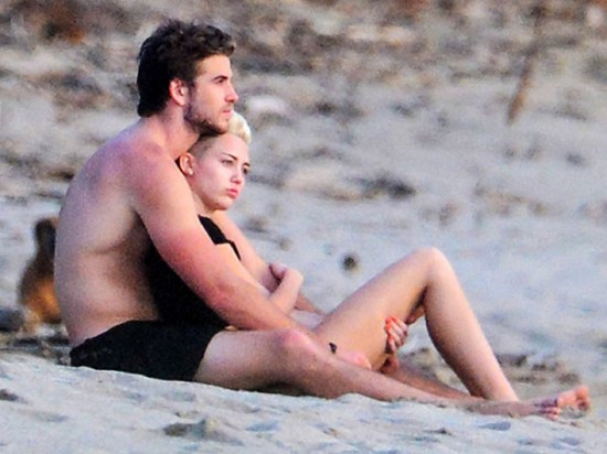 Miley Cyrus y su novio Liam Hemsworth, en la playa.